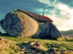It seems too strange to be real – a home emerging from a set of giant stones, seemingly cut out of the rock itself. Yet there it stands in rural Portgual with the pictures and video to prove it. No, it is not an optical illusion nor a fancy photo-editing job … this is the real deal.