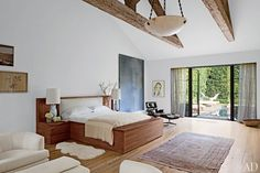 A vintage Eames chair and ottoman sit next to the custom-made walnut bed in the master suite, which is distinguished by reclaimed-oak ceiling trusses; the half-dome hanging light is by JF Chen, the large painting is by Van Pelt, and the watercolor portrait to its right is by Kim McCarty.