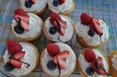 """""""Angel Fruit Cupcake"""" a light white cupcake with cream cheese frosting with berries on top."""