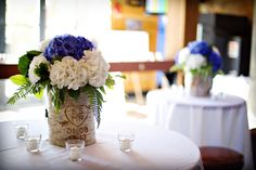 White and blue hydrangeas set in a custom log container with the wedding couples initials in a heart.  Photo ~ www.anastasiaphotography.ca See more of this Bliss wedding www.blissevent.ca