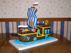 """Buccaneer """"Bucky"""" the Pirate Ship from Jake and the Neverland Pirates Cake. The cannon, 'wooden' part under the cannon, railings, slide, and large back piece were made from Chocolate Candy Clay.  The crow's nest is a Reese's Peanut Butter Cup.   I wasn't going to add the bell, but my kids insisted because 'that's how the ship talks to Jake!'  lol"""