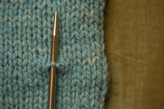 And bring it back out through the middle of the stitch above, picking up one strand.