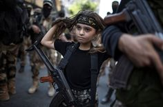 A Palestinian girl with a Kalashnikov rifle, amid Islamic Jihad militants in Gaza City