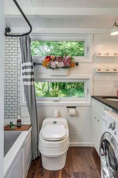 Space-saving pocket doors open to a bathroom complete with gorgeous subway tile, a Jacuzzi tub, a composting toilet, and even a washing machine. #refinery29 http://www.refinery29.com/2016/08/118903/new-frontier-alpha-tiny-home#slide-4