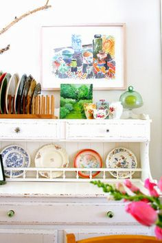 Floral-patterned plates on display in an open cabinet show off stylish dinnerware