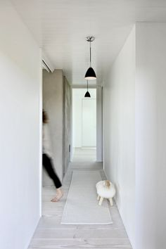 Beautiful and natural. White tongue and groove timber ceilings, white walls, oak white washed timber floors, natural runner rug, black pendant lights.