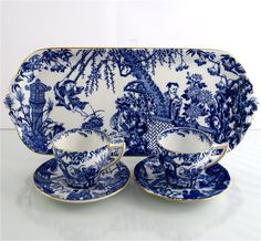 RARE SHAPED pair of Royal Crown Derby demitasse sets. The RCD Museum identifies this much older shape as 'Montreal', with its upturned pointed handles and very gently ribbed form. Displayed against a versatile  rectangular tray in same timeless Mikado design. Crown Derby's pure white porcelain with royal blue enamelling is extremely light and translucent with delicately gilded edges and handles. Pair of cups: $59. Sandwich tray: $149.