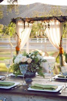 drapes as a backdrop are a nice frame to this al fresco table...