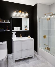 Clean, bright, black and white bathroom with marble hex floor and brass accents