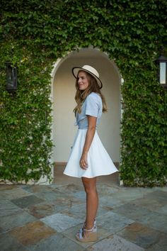 This combo of a light blue short sleeve button down shirt and a white pleated skirt is a safe bet for an effortlessly cool look. Go for a pair of baby blue canvas wedge sandals for a more relaxed feel.   Shop this look on Lookastic: https://lookastic.com/women/looks/light-blue-short-sleeve-button-down-shirt-white-skater-skirt-light-blue-wedge-sandals/19037   — Beige Straw Hat  — Light Blue Short Sleeve Button Down Shirt  — White Skater Skirt  — Light Blue Canvas Wedge Sandals