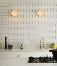 white contemporary English kitchen with Barber Wilsons silver gold goosneck bridge faucet - remodelista via atticmag