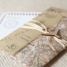 I ABSOLUTELY HAVE TO HAVE THIS!!! Vintage Air Mail Wedding Invitation - Wrapped w/ a vintage map of your location & sealed w/ raffia & a wooden airplane, this invite is sure to convey the vintage travel theme of your wedding – even the mailing envelope is printed w/ the air mail look – your guests will love getting this in their mailbox!