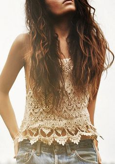 Curly haired model wearing beige lace crochet top