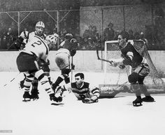 Canadian ice hockey player Tiny Thompson (born Cecil Thompson) (on the ice), goalkeeper for the Boston Bruins, reaches to make a save while his teammates, including Eddie Shore (#2), try to help, late 1920s or early 1930s.