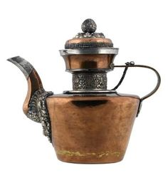 Teapot of copper, with lid attached by chain, straight flared sides with narrow neck and faceted spout, silver mounts with foliate designs, and bud-shaped knop, used for serving tea: Tibet, Lhasa, late 19th to early 20th century AD