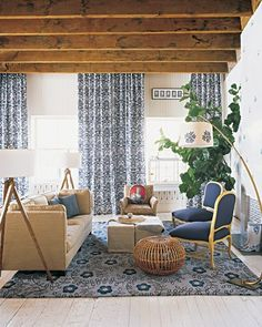 A graphic damask fabric was used for the floor-to-ceiling curtains in this living area. The rug is by British designer Neisha Crosland, and the slipper chairs are antiques.