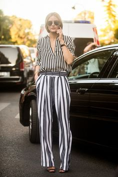 Olivia Palermo wears a striped shirt tucked into striped pants with Dior sunglasses.