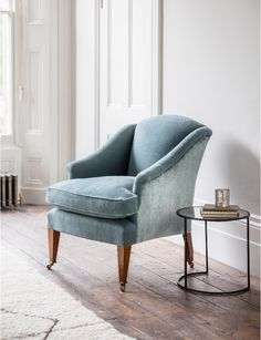 The Fielding chair is a compact and elegant armchair with scrolled arms and a high back. It has a separate seat cushion and tapered legs.