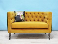 Handmade Loveseat tufted sofa upholstered with cotton printed fabrics. Mustard color fabrics on the seating area and bird printed fabrics on the