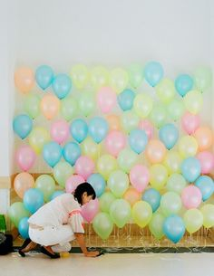 Pop!: A multicolored balloon wall made the backdrop for many a fun photo. Pearlized neon balloons were secured to the ground at staggered heights to get the look.