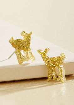 $20 Life is all about daily pick-me-ups, like the joy of adding these stud earrings to your ensemble! Their USA-made deer silhouettes, crafted in golden glitter bring a smile to your face as you bedeck yourself in this pretty pair by Vinca, making for a wonderfully quirky final touch!