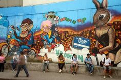 Oct 23, 2013; Rio de Janiero, BRA;  Locals sit along street in front of graffiti art near downtown Rio during the first world press briefing for the Rio 2016 Olympic Games.