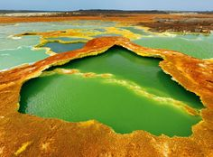 "Photograph by George Steinmetz  From ""Afar Depression,"" National Geographic, January 2012    Sulfur and algae turn hot springs into pools of living color. The water is condensation from hot gases rising from magma chambers. As the water evaporates, salts and minerals form a vivid crust."