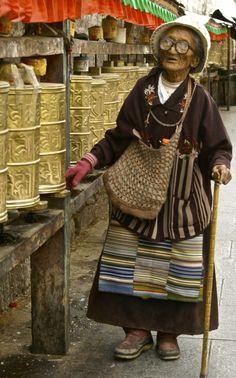 Buddhist pilgrim spinning prayer wheels in Lhasa.