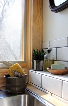 A little tiled ledge was a solution to a design problem that turned out to be a happy surprise element. The IKEA countertop couldn't extend any further, so this little shelf filled the space difference.  House Tour: A Peaceful Tiny Home on Wheels | Apartment Therapy