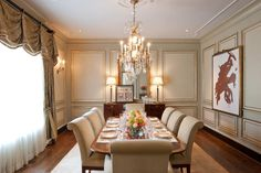 Neutral is far from boring in this formal dining room design by William C Johnson. Beautiful dark hardwood complements the traditional buffet. Additional traditional elements include the crystal chandelier and dramatic curtains. Neutral, upholstered dining chairs and a large piece of art on the wall bring contemporary flair to the room.