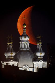 St. Petersburg, Russia, May 19, 2009--A full moon seems to hover above the dome of the Smolny Cathedral at dawn in a photo taken with a digital camera through the eyepiece of a telescope. | Photo by Dymitri Lovetsky/AP