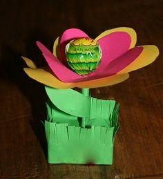 Een doosje rozijntjes, ingepakt in een groen vouwblaadje. De lollybloem vervolgens in het doosje geprikt (evt. voorprikken met een dikke naald of prikpen).