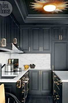 Dignified and dramatic, the black kitchen is accented with satin brass pulls, a black granite sink and a gold-hued sunburst light fixture. - My Home Decor Black Kitchen Cabinets, Black Kitchens, Home Kitchens, White Cabinets, Home Decor Kitchen, New Kitchen, Kitchen Ideas, Gold Kitchen, Kitchen Black