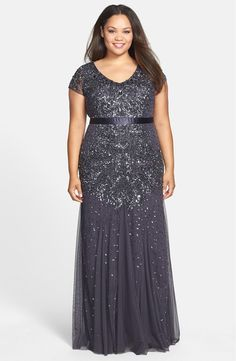 Sparkle and shimmer the night away in a sophisticated gown with a fitted cap-sleeve bodice and gracefully flared skirt. A simple satin band accentuates the waist.