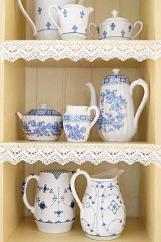 Na półkach kolekcja dzbanuszków i czajniczków.