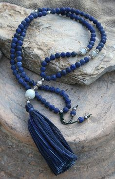 Mala necklace made ​​of 108, 8 mm - 0.315 inch, frosted lapis lazuli gemstones and decorated with faceted moonstone, silver color hematiet and metal bead caps. The guru bead is a 14 mm - 0.551 inch jade stone - look4treasures on Etsy.