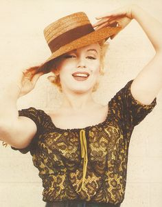 Marilyn Monroe photographed by Milton Greene, 1956. Sensational straw hat with brown grosgrain ribbon and a dramatic black-lace-over-citrine blouse.