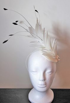 This is a stunning handmade fascinator with a large ivory feather. The fascinator is decorated with beautiful hand stitched cream pearls and swarovski crystal detailing as well as black coque feathers. It comes on an ivory sinamay base and ivory headband.  The fascinator is presented in a lovely gold fascinator box, which is ideal for storage and transportation!  This item would be perfect for a wedding or a day out at the races