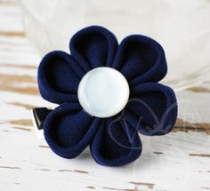 """""""New Navy"""" cherry blossom style kanzashi flower is a deep navy blue with a white vintage button center. This clip is a great way to subtly dress up a school uniform or work outfit.  """"New Navy"""" is secured to an alligator clip for easy wear in your hair, clipped to a lapel, purse or backpack."""