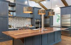 33 Blue and White Kitchens (Design Ideas) Contemporary kitchen with dark blue cabinets, large island with wood counter and bronzed drum pendant lights Dark Blue Kitchen Cabinets, Dark Blue Kitchens, Refacing Kitchen Cabinets, Kitchen Countertop Materials, Wood Cabinets, White Cabinets, Beige Kitchen, Bathroom Cabinetry, Kitchen Appliances