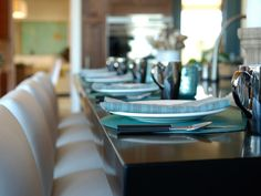 """The kitchen island is set for dinner with dinnerware and tabletop accessories to complement the turquoise color theme. """"The thing with place settings is – you're not committed. It's basically a place mat and a napkin and glasses, so if you want to use orange in there, you can use any color and change the look of that counter,"""" adds Woodrum."""