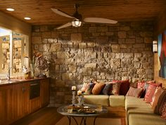 Sunroom with stone wall, L-seating, and a kitchenette.