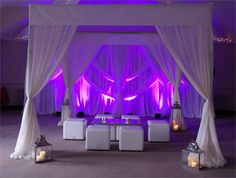 White Ibiza-style cabana, large and medium coach lanterns with pillar candle clusters, white cube chill-out furniture, white ornate swagged backdrop, and LED uplighters in purple by www.stressfreehire.com #venuetranformers