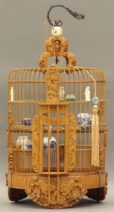 CHINESE CARVED BIRDCAGE with porcelain bowl/feeders circa 20th century height- 27 1/2""