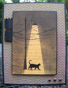 The paper is a orangy gold with a branch pattern on it. To create the pool of light coming from the street lamp I used post it notes to mask the light and then sponged around the post it notes with black ink. I used a grey maker to create a little shadow under the cat.