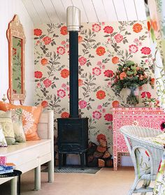This room offers such a pretty contrast between rusticity and flowery femininity. The woodstove (which is cozy) with the small woodpile makes you feel like you really are in the country, but the bright colours and flowers make it a pretty space too, while retaining that homey country feel! #country