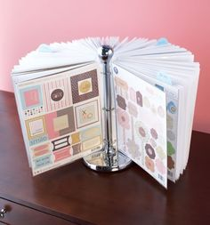 A paper towel holder with page protectors attached by rings. Display scrapbook supplies