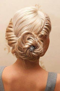 This is a simple twist braid, fish tail carefully pinned up in a bun, and whisped out to give it a flower affect.