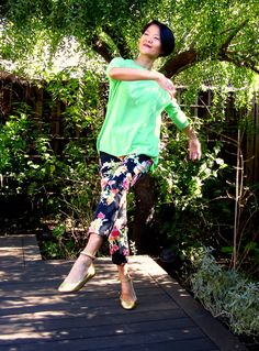 Green sweater with black flower pants and golden shoes