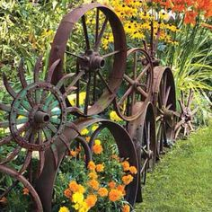 Love this idea for cute flower bed edging. We have some beautiful antique wheels like this in the store! Brilliant!